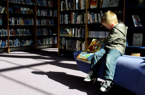 Picture of a kid reading in library.